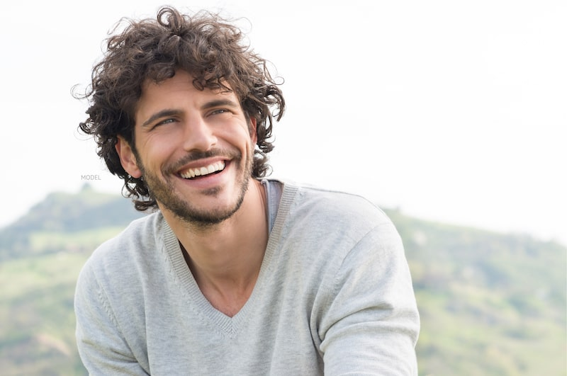 Man smiling while sitting outdoors with mountain in back.
